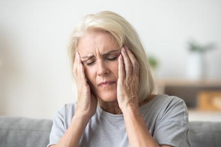 Malestar mujer mayor de mediana edad masajeando las sienes tocando la cabeza dolorida sintiendo un fuerte dolor de cabeza o concepto de migraña, triste, cansada, estresada, anciana, mayor, madura, sufrimiento, de, dolor, o, mareo Foto de archivo