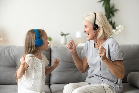 Happy senior grandmother and little kid granddaughter laughing listening to music in earphones dancing on sofa together, smiling grandchild and old grandma wearing headphones having fun enjoy song
