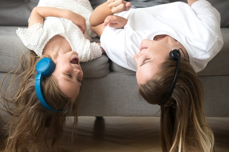Excited carefree mom and little child in headphones enjoy listening to music together, smiling kid daughter and happy mother lying upside down on sofa laughing having fun hearing songs in earphones