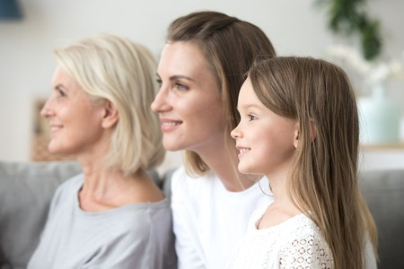 Smiling beautiful women in three generation family looking forward thinking of bright future, happy grandmother young mother and little child daughter dream of good, growing up, aging process concept 版權商用圖片 - 112483320
