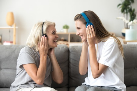 Happy senior mother and adult daughter laughing listening to music in wireless earphones together, smiling young old women wearing headphones having fun enjoy favorite song relaxing at home