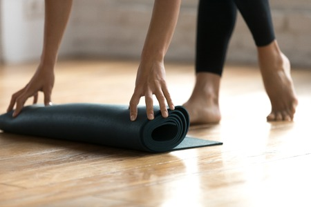 Close up woman hands unrolling mat preparing for fitness workout at gym studio. Sportive female folding rubber carpet after yoga session finishing sport training. Concept of active healthy lifestyle Stock Photo