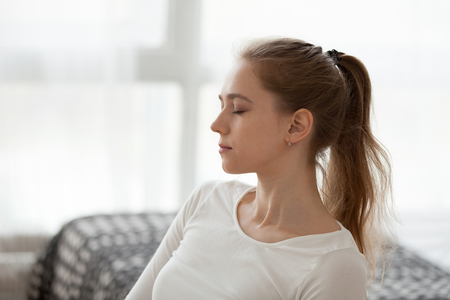 Close up of calm young female sitting with eyes closed meditating indoors, peaceful girl relaxing or having rest, breathing and controlling emotions, concentrated millennial woman thinking or dreaming