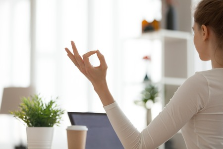 Close up of focused woman meditating at home, hands in mudra position, concentrated girl practice yoga in apartment sitting in lotus pose, breathing calm and controlling emotions. Relaxation concept