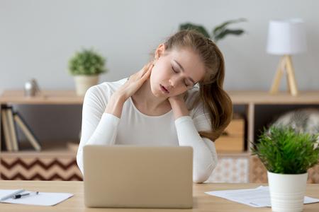 Mujer joven agotada sentada en el escritorio de la oficina en casa masajeando el cuello sintiendo dolor, la niña cansada sufre de dolor de espalda o tensión, tiene síntomas de espasmo, la mujer milenaria se siente mal por el estilo de vida sedentario Foto de archivo