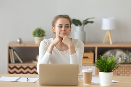 Dreamy young female sit at home office desk looking to side thinking of future success, thoughtful happy girl distracted from work dreaming of achievement, smiling woman imagine or visualize