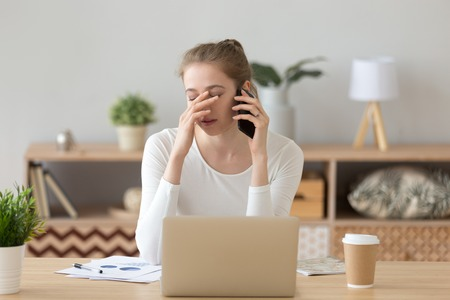 Upset girl working on computer at home desk talking on smartphone hearing bad news, disappointed female annoyed speaking on phone while studying at laptop, young woman get unpleasant call on cell 스톡 콘텐츠