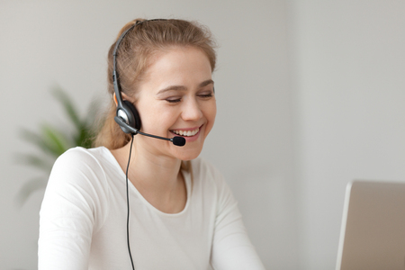 Smiling young female wearing headset making video call at laptop, happy girl in earphones working from home talking with customer, millennial woman or call center agent consulting client online
