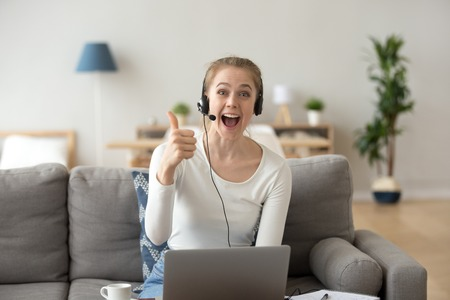 Portrait of excited young female wearing headset show thumbs up to camera recommending online course or training, happy girl in earphones sit with laptop at home gesture liking educational program