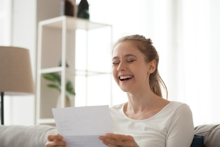 Excited girl sit on couch reading letter knowing good news, happy young female look through paperwork receive positive feedback, smiling woman get document or paper with affirmative response