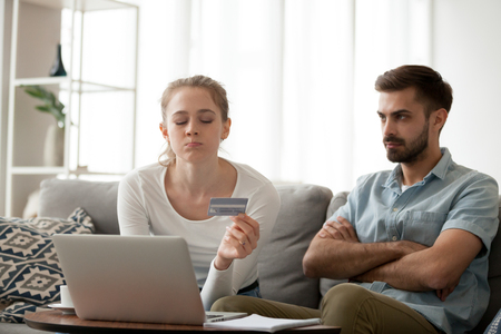 Stubborn millennial wife have fight with husband over online shopping, young woman use credit card making purchases on internet, angry husband mad at spouse for spending money. Family conflict concept Stock Photo