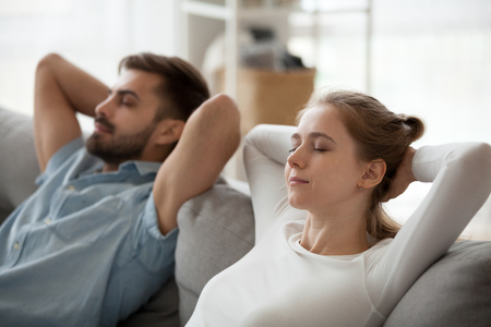 Close up of peaceful man and woman relax on cozy couch at home hands over head, mindful millennial couple lying on comfortable sofa resting with eyes closed, husband and wife take nap in living room 写真素材