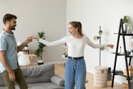Happy millennial couple having fun at home together, smiling husband and wife dancing in living room laughing, excited man and woman waltz and swirl, moving to the rhythm. Relationship goal concept Stok Fotoğraf