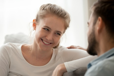Close up of loving young woman look at beloved spouse relaxing on couch together, happy millennial wife admire husband cuddling on sofa at home, smiling female enjoy tender moment with spouse Stock Photo