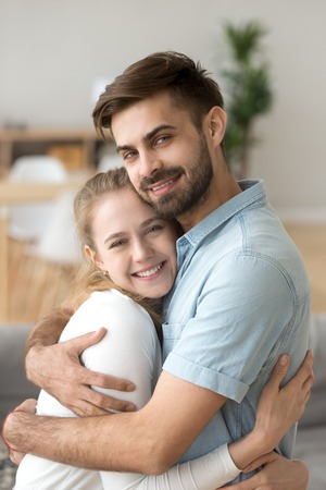 Portrait of young happy husband and wife hug looking at camera, smiling millennial couple embrace at home posing for family picture, caring man holding beloved woman in arms showing love and support 版權商用圖片