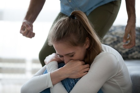 Frightened crying young woman suffering from aggressive husband behavior, man scare wife with fist intending to hit or beat, mad male tyrant threaten upset girlfriend. Domestic violence, abuse concept
