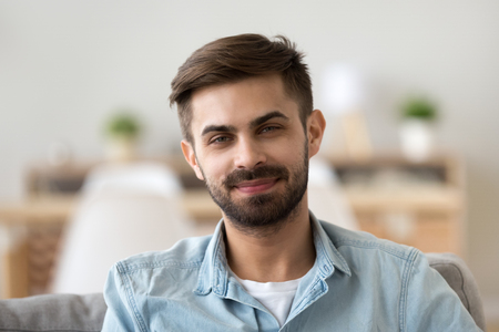 Portrait of happy millennial man looking at camera relaxing at home, headshot of smiling young male posing for picture indoors, confident guy making picture sitting on couch in apartment