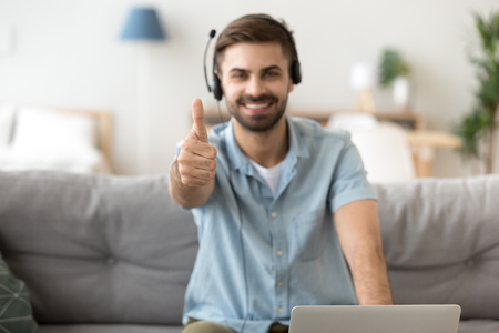 Excited millennial man show thumbs up sitting on couch using laptop, happy young male in headset gesture working from home recommending online course or training, guy student give good recommendation