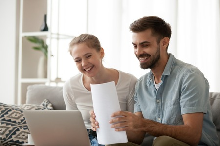 Happy husband and wife read good news online at laptop, millennial couple smiling holding documents receiving positive decision from bank, man and woman get email having mortgage or loan approved Banco de Imagens