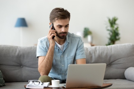 Serious male sit on couch using laptop talking on smartphone, focused millennial man working on computer from home consulting client on cell, busy worker speak on mobile solving problems online Stock Photo