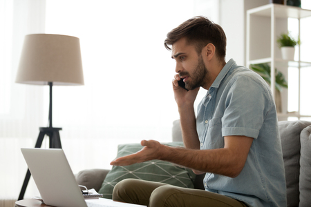 Confused male having computer problems talk on mobile with customer support, frustrated millennial man speak on smartphone managing computer malfunction working online from home Stock Photo