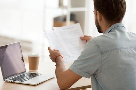 Vista posteriore dell'uomo concentrato seduto al tavolo dell'ufficio che lavora al computer portatile guardando documenti cartacei, concentrato maschile in possesso di scartoffie considerando il problema, impegnato a usare il computer e a bere caffè