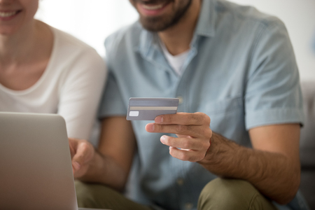 Close up of man holding credit card in hands shopping together with beloved woman, happy couple making purchases via internet from home, smiling husband and wife buy using laptop at home 스톡 콘텐츠