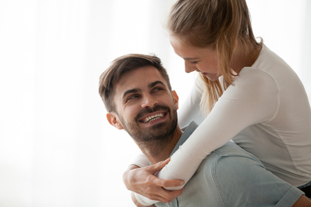 Smiling man and woman having fun spending time together at home, happy wife piggyback beloved husband looking each other in the eyes, excited couple cuddling and laughing enjoying free time Stok Fotoğraf