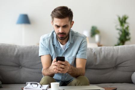 El hombre milenario se sienta en el sofá con un teléfono inteligente sorprendido al leer noticias en línea, el hombre sorprendido recibe un mensaje de ruptura o texto en el teléfono móvil, el tipo confundido que sostiene la celda ve la notificación de advertencia de virus