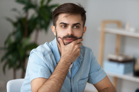 Close up of pensive millennial man sit at office home desk thinking of problem solution, thoughtful male lost in thoughts ponder or consider plan implementation, guy look in distance making decision Stock Photo