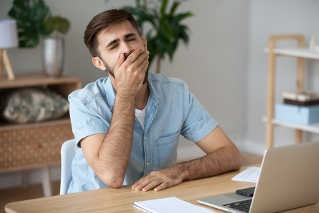 Exhausted male worker sit at home office desk near laptop yawning working too long, tired man feel lazy and unmotivated distracted from computer job, student sigh have sleep deprivation or energy lack Stock Photo