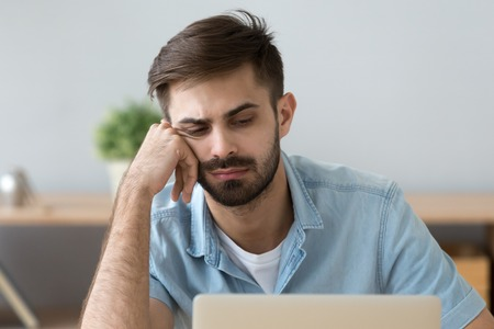Close up of millennial man feel bored looking at laptop screen thinking of something, sad male worker sit at workplace gaze at computer having no motivation, lazy student lack energy to study or work Stock Photo