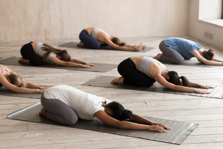 Group of young sporty diverse people doing yoga Child exercise, Balasana pose, working out, indoor full length, mixed race female students training at club or studio. Well being, wellness concept Stock Photo
