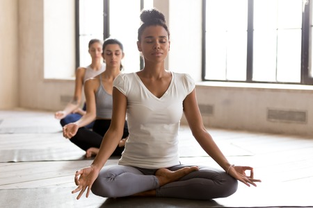 Yogi black woman and row of diverse group of sporty people doing yoga Padmasana exercise, Lotus pose, working out indoor, mixed race female students at training studio. Well being, wellness concept