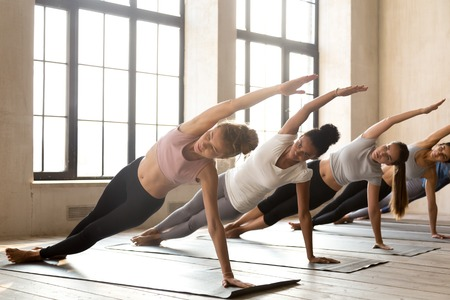 Group of young diverse sporty people doing yoga Vasisthasana exercise, Side Plank pose, working out, indoor full length, mixed race female students training at club or studio. Well being, wellness concept Stock Photo