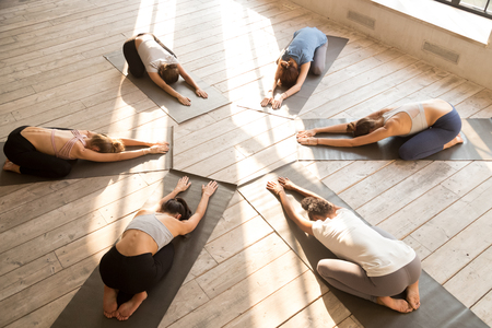 Group of diverse young sporty people practicing yoga, doing Child exercise, Balasana pose, mixed race female students training at club, yoga studio, top view. Well being, wellness concept, full length Stockfoto