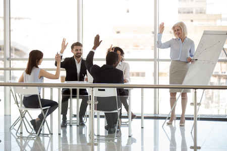 Happy diverse business people team interns group and mature mentor coach raising hands at office training as concept of teambuilding engagement, supporting agreement, knowledge, voting, involvement Stockfoto - 112485097