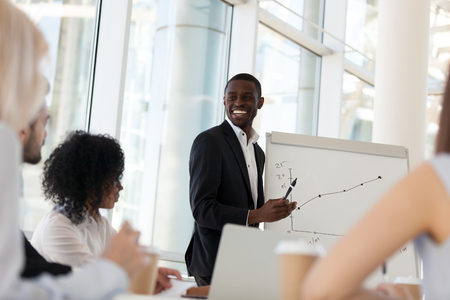 Smiling friendly african american businessman mentor giving presentation at diverse team office training, happy black coach satisfied with growth laughs speaks about good work result at group meeting Stock Photo