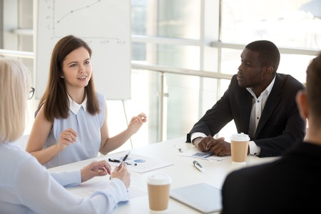 Female employee team leader speaking at diverse group meeting, multiracial partners negotiating, office people talking discussing project or business offer at briefing with millennial coach advisor