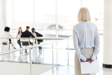 Vista posteriore a stressato nervoso di mezza età senior vecchia donna d'affari richiedente aspetta il colloquio di lavoro tenendo i documenti dietro la schiena preparandosi per le prestazioni si sentono paura del concetto di paura di parlare in pubblico.