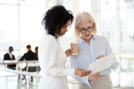 Senior mature caucasian female executive ceo discuss report with young mixed race black colleague, serious old aged mentor reads paper explains business plan to african employee intern talk in office Banque d'images - 112485294