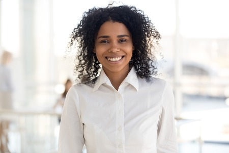 Smiling young african american woman employee, intern girl, worker or student looking at camera in modern office, happy millennial mixed race black professional, business coach headshot portrait