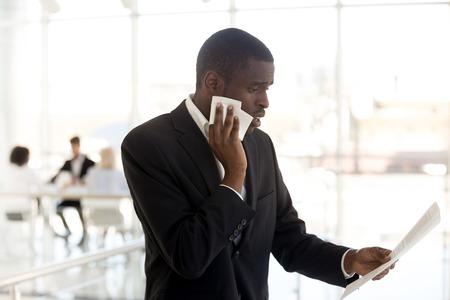Hombre de negocios afroamericano nervioso asustado sudando limpiando la cara sintiéndose estresado asustado esperando una entrevista de trabajo, orador masculino negro preocupado leyendo papel preparándose para hablar en público concepto de miedo