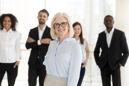 Portrait of happy older woman middle aged company ceo, female corporate leader mentor looking in camera with team subordinates, friendly mature executive boss, hr or business coach posing in office Stock Photo