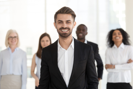 Smiling excited young businessman in suit looking at camera posing with diverse team, millennial professional manager, corporate leader, successful executive, happy ceo or business coach portrait Stock Photo