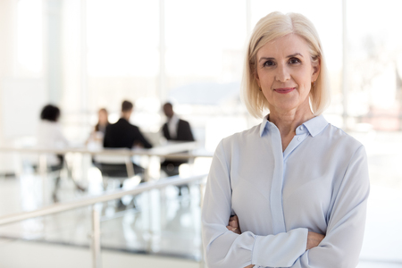 Confident mature businesswoman looking at camera, middle aged company ceo director, experienced senior female professional, old lady business coach team leader posing in office, headshot portrait Stockfoto
