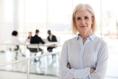 Femme d'affaires mûre et confiante regardant la caméra, directrice générale d'une entreprise d'âge moyen, professionnelle senior expérimentée, chef d'équipe d'entraîneurs d'affaires de vieille dame posant au bureau, portrait en tête Banque d'images