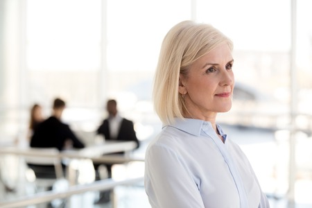Thoughtful dreamy middle aged businesswoman looking away thinking of new goals opportunities in office, serious mature senior old woman planning future, dreaming of success, business vision concept 免版税图像 - 112485483