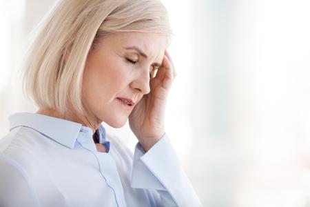 Moe overstuur volwassen oude zakenvrouw die lijdt aan sterke chronische hoofdpijn migraine of geheugenverlies op het werk, gestrest duizelig vermoeide senior vrouw kantoormedewerker van middelbare leeftijd voelt pijn in pijnlijk hoofd