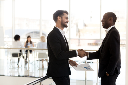 Diverse millennial businessmen shaking hands get acquainted introducing making first impression standing in modern office, happy african and caucasian partners handshaking smiling talking greeting